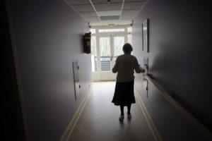 Elderly person walking in unlit corridor